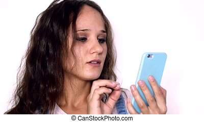 Young beautiful woman with curly hair uses mobile phone isolated on a white background.