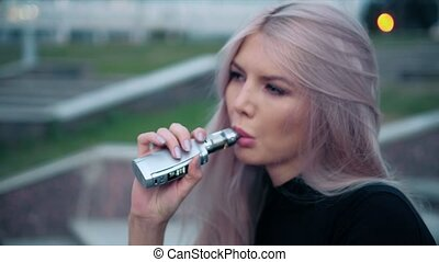 Young beautiful woman with fashion makeup at the outdoor with a with vapor from electronic cigarette 4k