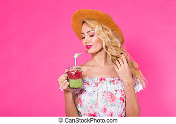 Young beautiful woman with green smoothie on pink background