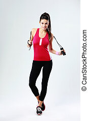 Young beautiful woman with jumping rope on a gray background