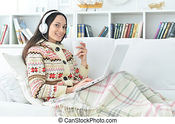 Young beautiful woman with laptop on sofa at home