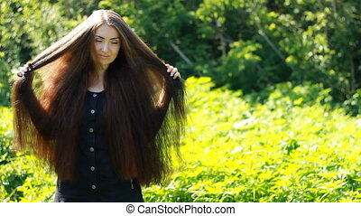 Young beautiful woman with long hair in outdoor. Hairstyl. Portrait of a girl with brown hair.