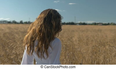 Young beautiful woman with long hair, in a white dress is walking along a field with wheat.
