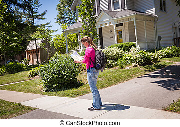 Young beautiful woman with map in hand to find the right path in town