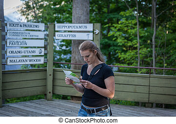 Young beautiful woman with map in hand to find the right path in Zoo