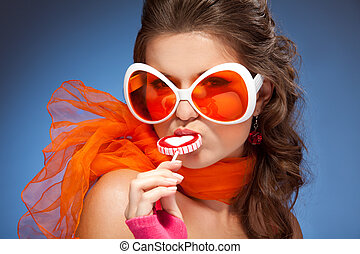 Young beautiful woman with orange scarf lick lollipop and wearing huge sunglasses