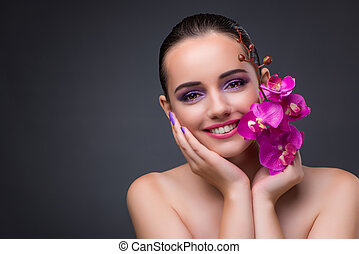 Young beautiful woman with orchid flower