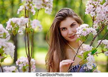 Young Beautiful Woman with Pink Sakura Flowers