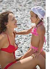 young beautiful woman with pretty little girl in white hat on stony beach