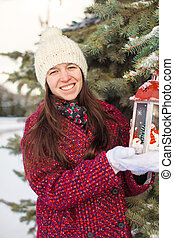 Young beautiful woman with red Christmas lantern in the snow