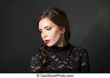 Young beautiful woman with red lips makeup hair on black background