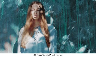 young beautiful woman with shadows on face with long red hair and blue shirt