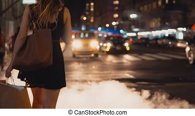 Young beautiful woman with shopping bags crossing the traffic road with manhole cover, smoke in New York, America.