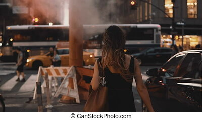 Young beautiful woman with shopping bags walking in downtown of New York, America, crossing the traffic road.