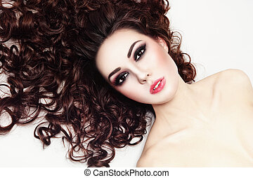 Young beautiful woman with smoky eye make-up and long curly hair