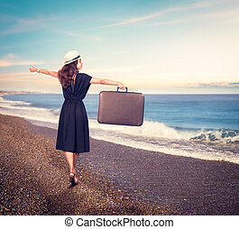 Young beautiful woman with suitcase on the beach.