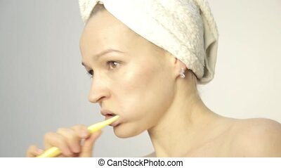 Young beautiful woman with towel on a head brushing her teeth and dancing