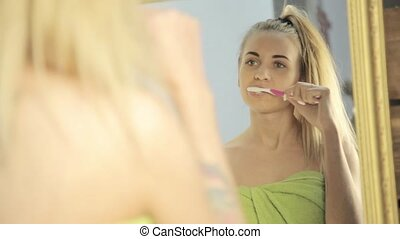 Young beautiful woman with towel on a head brushing her teeth in bathroom