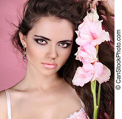 Young beautiful woman with white flower over pink