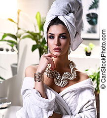 Young beautiful woman with white towel on head looking at the mirror wearing bathrobe and gold pearl jewellery