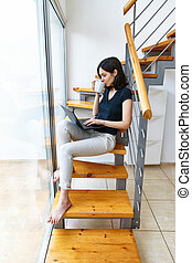 Young beautiful woman working on laptop and drinking hot coffee sitting on stairs
