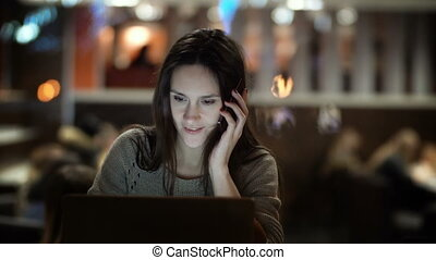 Young beautiful woman working on laptop in evening. Brunette female sitting in cafe and talking on smartphone.