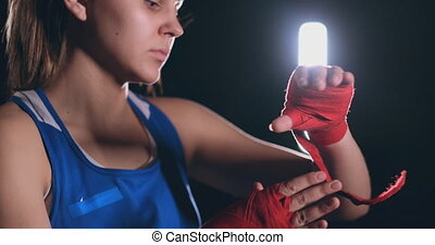Young beautiful woman wrapping hands with black boxing wraps...