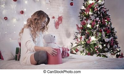 Young beautiful woman wraps Christmas gifts sitting on the bed near Christmas tree