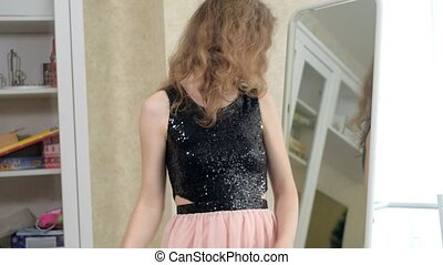 Young beautiful woman zipping up her elegant black dress looking in a large mirror
