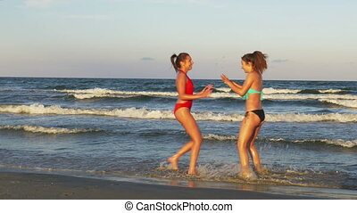 Young beautiful women enjoying teasing one another on a beautiful wet sandy beach
