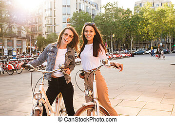 Young beautiful women friends outdoors on bicycles