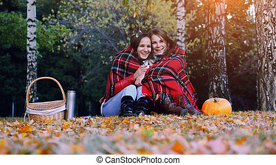 Young beautiful women sitting on picnic bundled up in a blanket drinking hot tea from thermos in autumn park. Girls rug near the pumpkin of Halloween theme