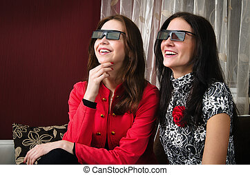 young beautiful women watching 3D TV at home