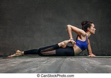 Young beautiful yoga female posing in studio