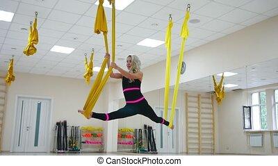 Young beautiful yogi woman doing aerial yoga practice in...