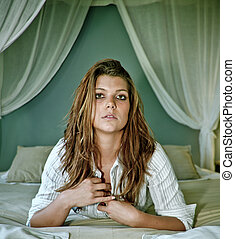 Young beautifull lady with long hair on romantic bed