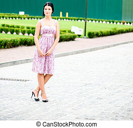 Young beautifull woman standing in a dress