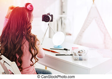 Young beauty blogger sitting in front of camera while making nice hairstyle for party