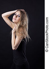 Young beauty blond girl in black dress look at you
