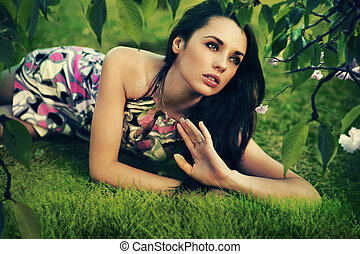 Young beauty brunette laying on the grass