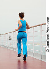 young beauty girl in sport dress running on cruise liner deck, view from back