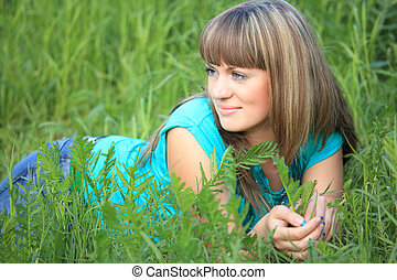 young beauty girl lies in grass