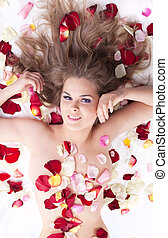 Young beauty nude woman lay in rose petals