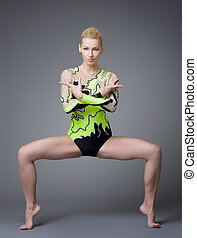 Young beauty woman as gymnast stand on splits