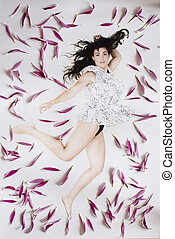 young beauty woman flying in jump with black hair in flower peta