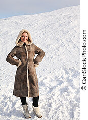 young beauty woman in long coat standing on snowy area and smiling, winter day