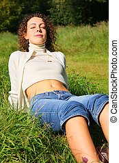 young beauty woman outdoor sits on grass