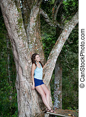 Young beauty woman posing at big tree in jungle forest