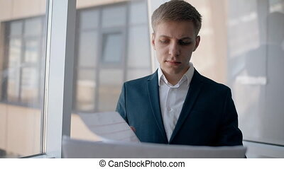 Young beginning entrepreneur is reading contract during working day in office interior.