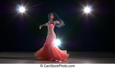 Young belly dancer girl continue dancing on black, back light, slow motion